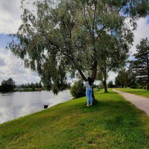Nainen seisoo joenrannalla selin kameraan päin.