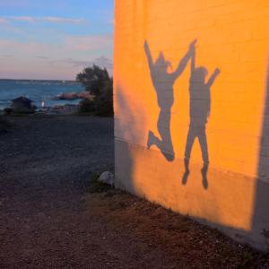 Vasemmalla pilkottaa meri matalien rantakasvien takaa, oikealla Ykspihlajan majakan seinä, johon laskevan auringon valo luo varjokuvan ilmaan hypähtävistä kahdesta lapsesta.