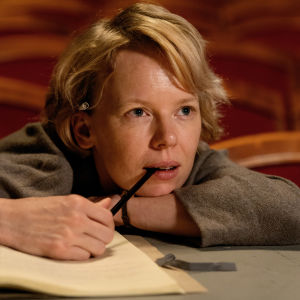Tove (Alma Pöysti) sitter vid scenkanten och ser fundersam ut.