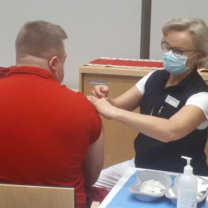 Hoitaja antaa rokotuksen miehelle.