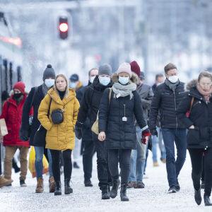 Människor i munskydd stiger ut ur ett tåg i Helsingfors.
