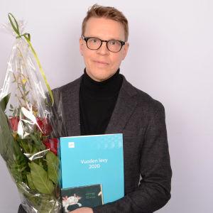 Petri Kumela poseeraa kukkapuskan kanssa.