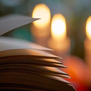 En bok uppslagen i ljuset av ett ljus.