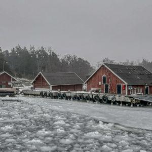Själö förbindelsebåtsbrygga med röda byggnader i ett isigt vinterväder.