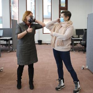 Kaksi naista tervehtii toimistossa toisiaan kyynärpäätervehdyksellä