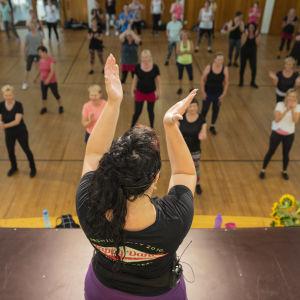 Dansinstruktör på scen klappar i händerna inför sina elever.