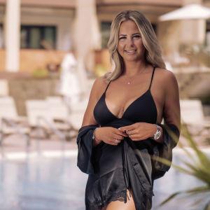 En kvinna iklädd svart bikini står framför ett lyxhotell.