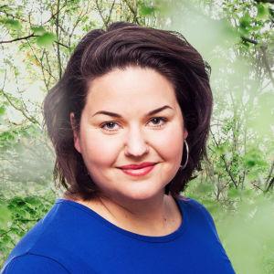 Daniela Franzell småler in i kameran framför en grönskande bakgrund.