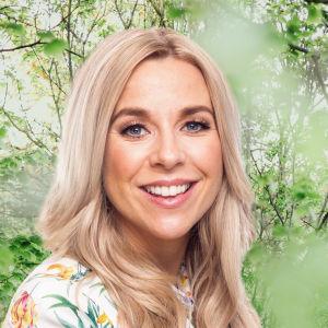 Krista Siegfrids småler in i kameran framför en grönskande bakgrund.