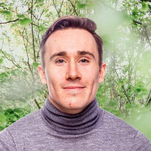 Kristian Lever småler in i kameran framför en grönskande bakgrund.