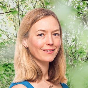 Linda Zilliacus småler in i kameran framför en grönskande bakgrund.