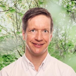 Markus Haakana småler in i kameran framför en grönskande bakgrund.