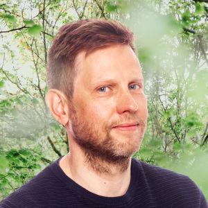 Kjell Carlström småler in i kameran. Bakgrunden är en grönskande skogsdunge.