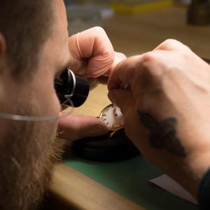 Lähikuva kelloseppä Kari-Matti Ratsulasta korjaamassa vanhaa kelloa