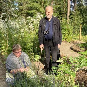 Kuvassa kaksi henkilöä puutarhassa. Toinen seisoo ja toinen on polvillaan.