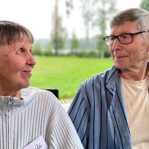 Mies ja nainen istuvat vierekkäin ja katsovat toisiaan silmiin