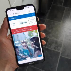 En person håller i en telefon. På skärmen syns Min Kanta-sidan.