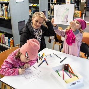 Barn och mamma som sitter och ritar i ett bibliotek.