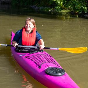 En kvinna i en rosafärgad kajak i en å. Vattnet ganska grumligt. Det är Ingå å.