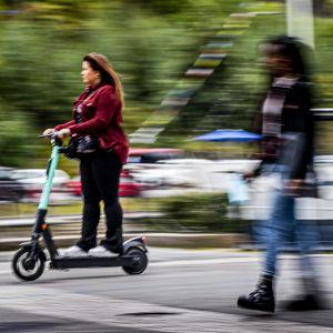 en suddig bild på en tjej som åker elsparkcykel