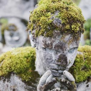 Mossklädd betongstaty föreställande person som lutar ansiktet i knäppta händer.