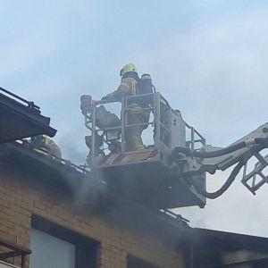 Brandmän släcker en eld på ett tak till ett tegelhus.