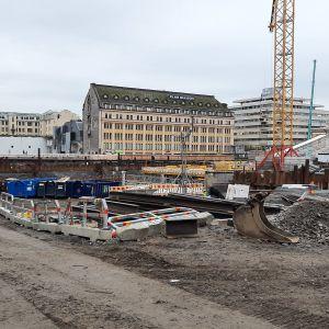 Byggkonstruktioner, ställningar, lastbilsflak och en byggkran står i gropen till det som byggs till en torgparkering under Salutorget i Åbo.