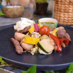 En svart flat tallrik med en portion vinkokta grönsaker och kött i munsbitar. På tallriken finns också en tjock vit sås och en liten sål med en mörkbrun sås.