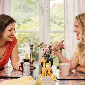 Eva Frantz och Hannah Norrena sitter vid ett köksbord och skrattar.