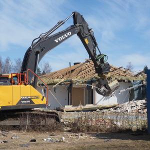 Kaivuri purkaa vuokrataloyhtiön rakennusta.