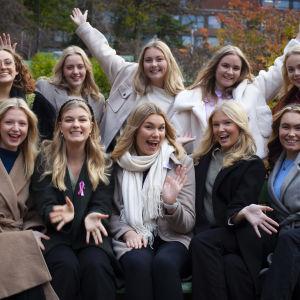 Luciakandidaterna år 2021 poserar på en bänk.