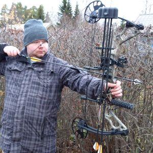 Nuori mies jännittää metsästysjousta siirtolapuutarhassa.