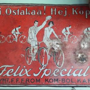En röd gammal skylt i metall som visar ett par som cyklar. På skylten står det: Hej! Köp Felix Special.