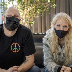 Paleface ja Susan Aho istuvat sohvalla vierekkäin maskit päällä.