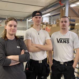 Essi Leminen, Wili Ojala ja Miika Mutka seisovat rakennusalan yrityksen varastossa työvaatteet päällä.