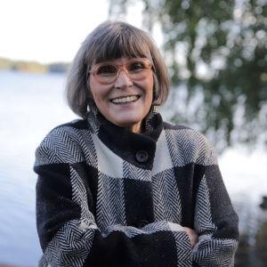 Nainen hymyilee kameralle, taustalla järvimaisema