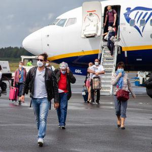 Italiasta tulleita ihmisiä kasvomaskeissa kävelee lentokoneesta Lappeenrannan lentoasemalla 1.7.2020.
