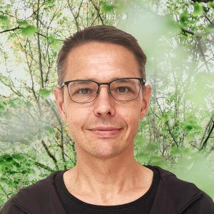 Olof Schybergson småler in i kameran. Bakgrunden är en grönskande skogsdunge.