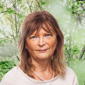 Annika Hällsten ser rakt in i kameran. Bakgrunden är en grönskande skogsdunge.