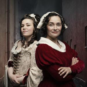 Julia Korander och Nina Hukkinen som barnmorskorna Maria Lizelia och Catharina Aspelin år 1759.