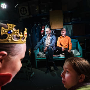 Två människor sitter på en soffa i bakgrunden. I förgrunden två skådespelare på scen.