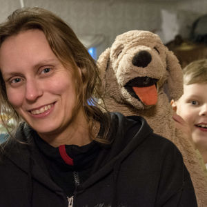 En kvinna ler i förgrunden, bakom henne en pojke med stor leksakshund.