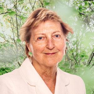 Ulla Tillander-Godenhielm småler in i kameran framför en grönskande bakgrund.