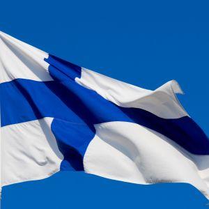 Suomen lippu sinitaivasta vasten.