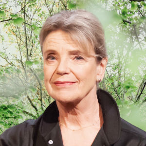 Stina Ekblad småler in i kameran. Bakgrunden är en grön skogsdunge.