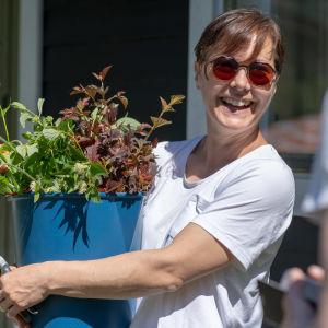 Puutarhuri Anna Palasmaa hymyilee sylissään ämpärillinen leikkokukkia