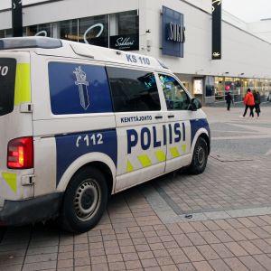 En polisbil i centrum av en stad. I bakgrunden syns ett köpcenter.