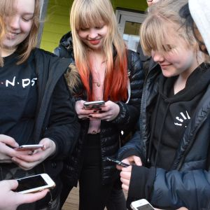 Valkeavuoren koululaisia kännykät kädessä koulun välitunnilla.