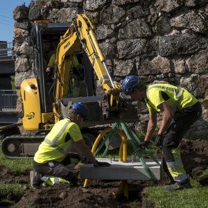 Työmiehet asentavat linnanraunioille lampunjalkaa.
