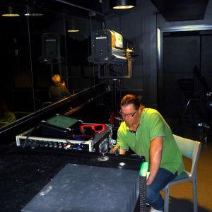 Janne Lindgård, en man med glasögon och grön t-skjorta, sitter vid en filmprojektor i ett nästan helt mörkt rum.